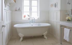 A double ended Roll Top Bath in a traditional bathroom with wooden panels
