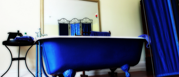 A lovely cast iron roll top bath in a bedroom